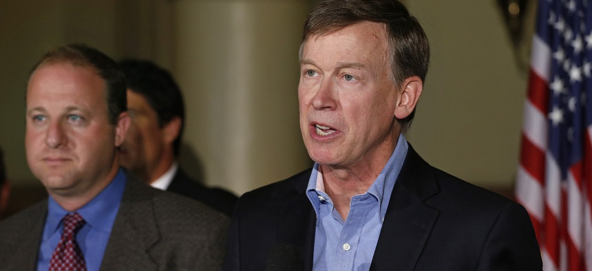 Colo. Gov. John Hickenlooper, right, speaks as U.S. Rep. Jared Polis, D-Colo., left, stands nearby, during a news conference about fracking, at the Capitol in Denver, Monday Aug. 4, 2014.