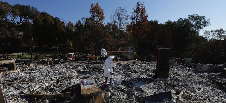 Shelly Rust, foreground, and her husband David search through the remains of their home destroyed by wildfires in Santa Rosa, Calif.