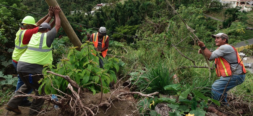 Public Works Sub-Director Ramon Mendez, wearing a hard hat at left, works with local municipal workers to install a new electrical post to return power to a home without any, four months after Hurricane Maria hit Puerto Rico.