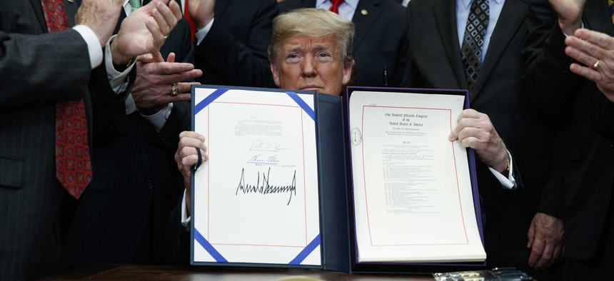 "President Donald Trump shows off the ""Economic Growth, Regulatory Relief, and Consumer Protection Act,"" in the Roosevelt Room of the White House, Thursday, May 24, 2018, in Washington."