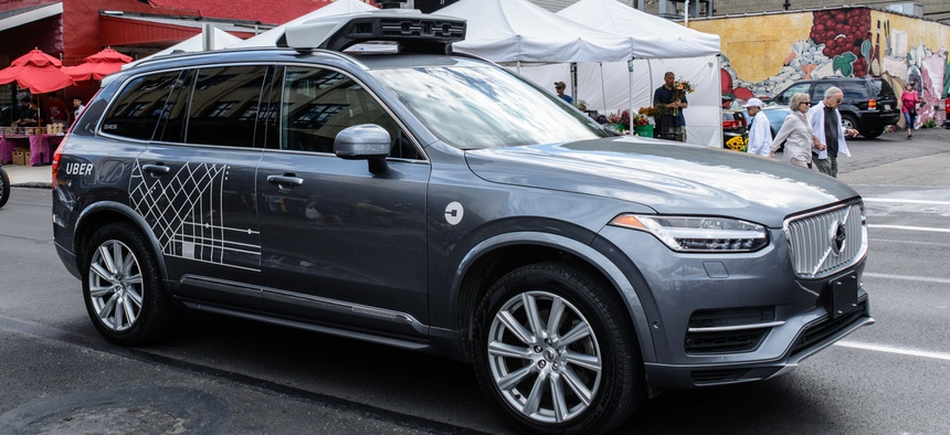 An Uber autonomous vehicle travels along Penn Avenue in Pittsburgh's Strip District.