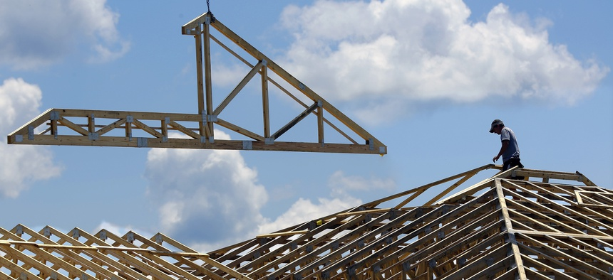 In this Thursday, July 17, 2014 photo construction workers build a commercial complex in Springfield, Ill.