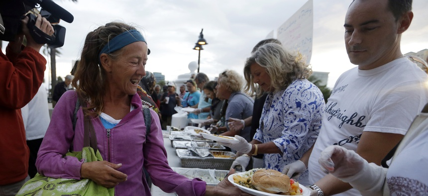 In this Nov. 5, 2014, file photo, members of the homeless community are served meals by advocates in Fort Lauderdale, Fla.