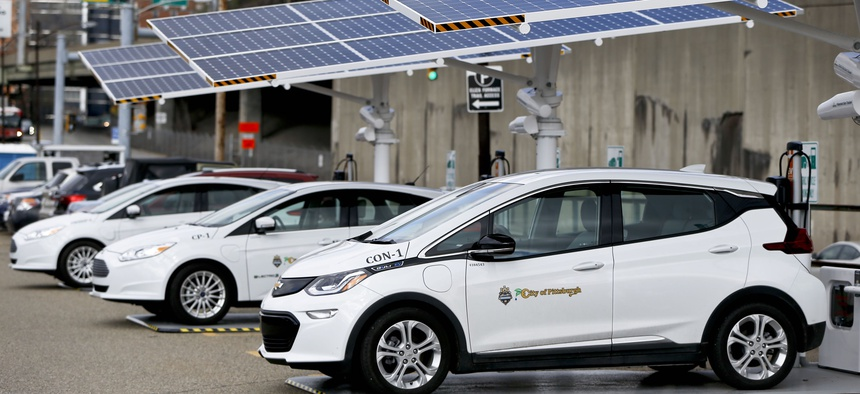 Some of the city of Pittsburgh's fleet of electrical vehicles are parked under solar charging panels before a news conference announcing the facility debut, Wednesday, April 18, 2018, in Pittsburgh.
