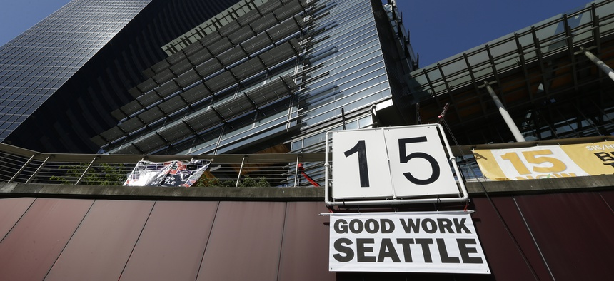 """A sign that reads """"15 Good Work Seattle"""" is displayed below Seattle City Hall, right, and the Columbia Center building, left, Monday, June 2, 2014, after the Seattle City Council passed a $15 minimum wage measure."""