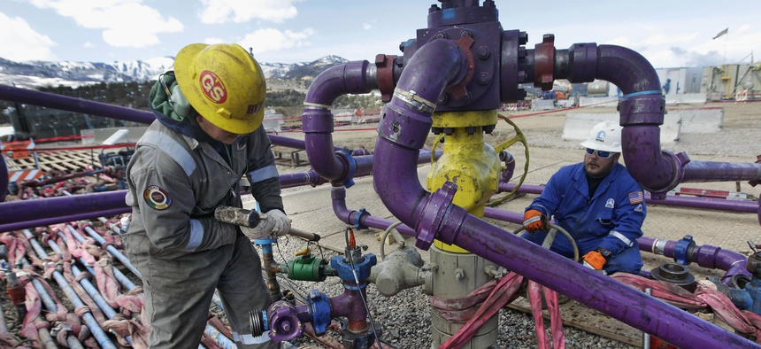 In this March 29, 2013 file photo, workers tend to a well head during a hydraulic fracturing operation outside Rifle, in western Colorado.