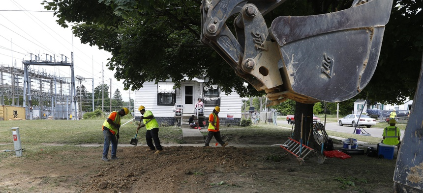 In this July 20, 2018, file photo, workers back fill a hole used to replace lead pipe with copper water supply lines to a home in Flint, Mich.