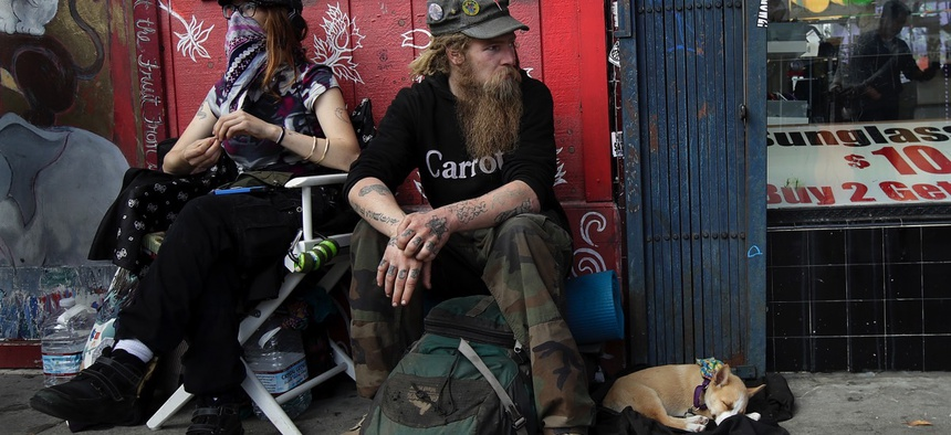 Homeless man Stormy Nichole Day, left, sits on a sidewalk on Haight Street with Nord and his dog Hobo on Oct. 1, 2018, in San Francisco.