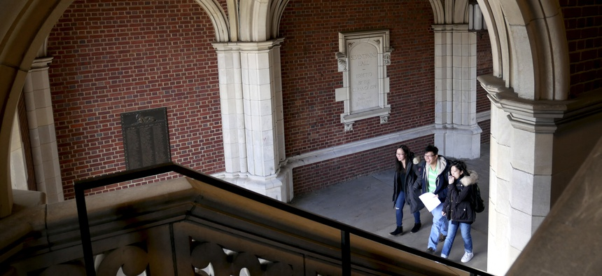 People walk through one of the famous arches of Princeton University in Princeton, N.J., April 5, 2018.