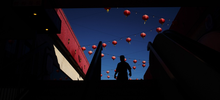 A shopper is silhouetted as he walks through a mall adorned with some Chinese lanterns in the Chinatown section of Los Angeles.