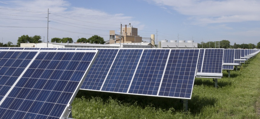 In this May 31, 2018, photo, a solar panel array collects sun light with the Fremont, Neb., power plant seen behind it.
