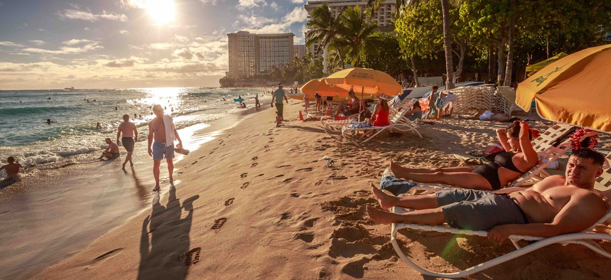 """Beachgoers in Hawaii, a state that has consistently performed well on Gallup's """"well-being"""" index."""