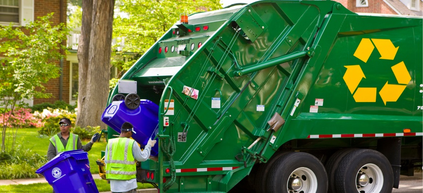 Workers empty recycling bins into a truck in Arlington, Virginia