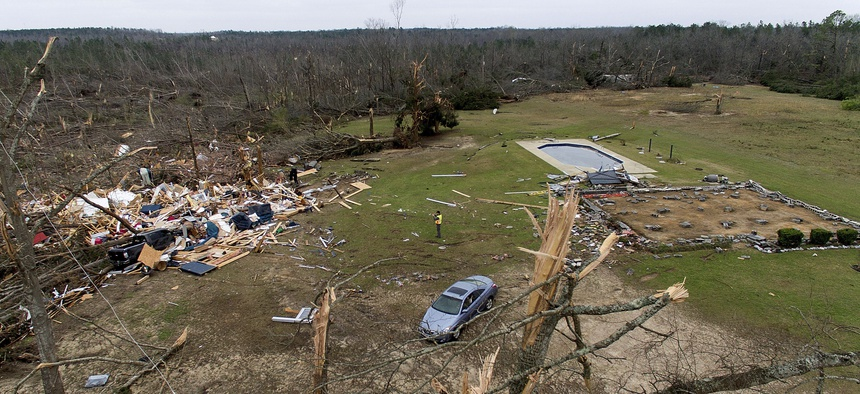 Debris from a home litters a yard the day after a tornado blew it off its foundation, at right, in Beauregard, Ala., Monday, March 4, 2019.