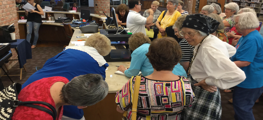 Members of the El Progreso Club crowd around the library's 3D printer