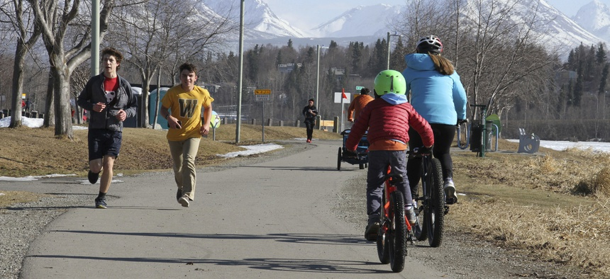 This April 3, 2019, photo shows people running and biking at Westchester Lagoon in Anchorage, Alaska, with the snow-covered Chugach Mountains in the distance. Much of Anchorage's snow disappeared as Alaska experienced unseasonably warm weather in March.