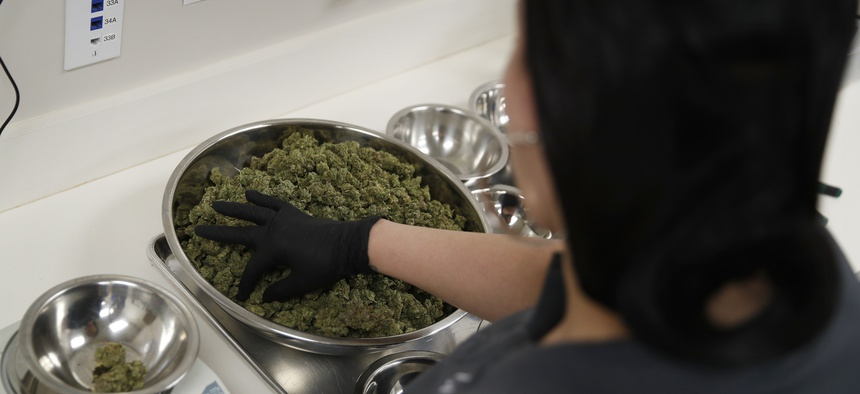 A worker sorts marijuana at the Blum marijuana dispensary in Las Vegas.