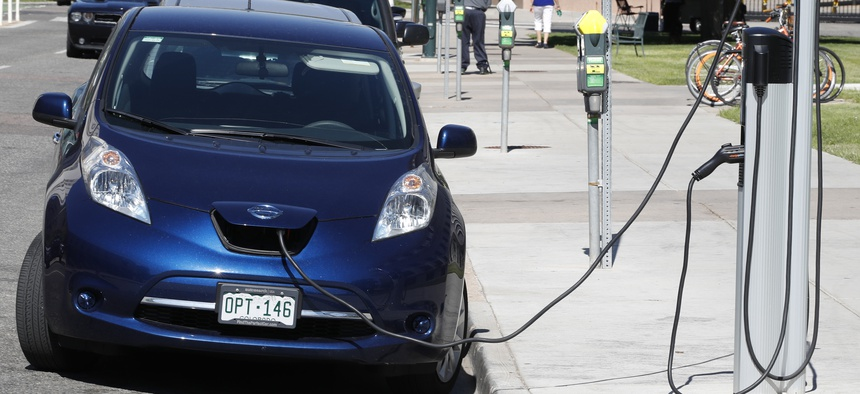 A Nissan Leaf charges at a recharge station while parked by the Denver City/County Building in downtown Denver.