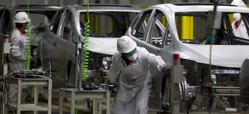 In this Feb. 21, 2014 file photo, employees at work in the new multibillion-dollar Honda car plant in Celaya, in the central Mexican state of Guanajuato.