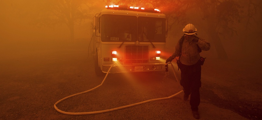 A firefighter rushes to save a home as the River Fire tears through Lakeport, Calif., on Tuesday, July 31, 2018.