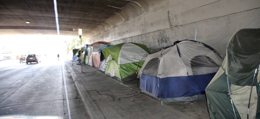 A row of tents stationed under a viaduct in LA.