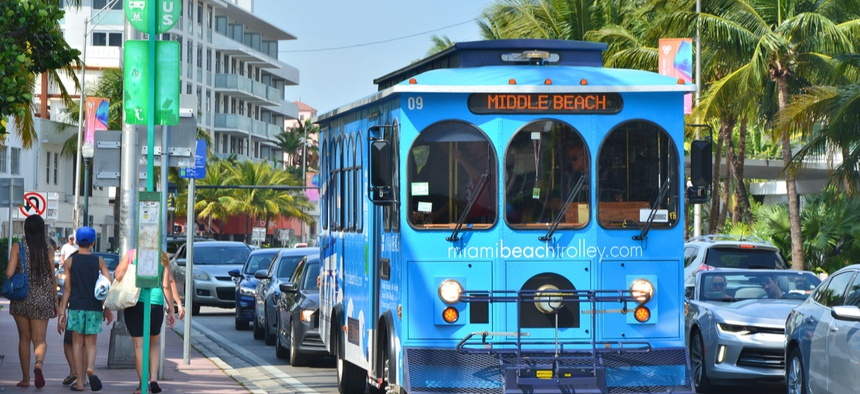 A blue trolley on the bus stop in Miami Beach.