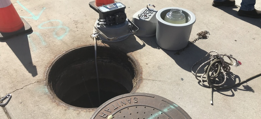 A sampler tapping directly into the sewer through a manhole in Tempe, Arizona. A glass jar of wastewater is also pictured.