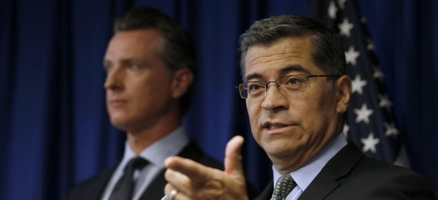 California Attorney General Xavier Becerra, right, flanked by Gov. Gavin Newsom, responds to a question concerning the Trump administration's pledge to revoke California's authority to set vehicle emissions standards.