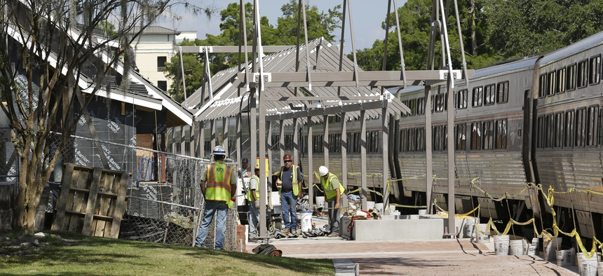 In this Monday, Oct. 28, 2013 photo, construction workers make progress on the SunRail station as an Amtrak train stops at the next door Amtrak station to pick up passengers in Winter Park, Fla.