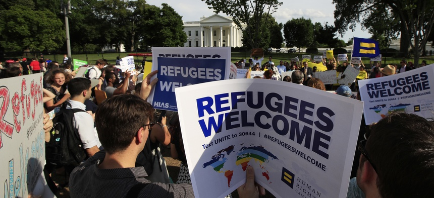 In this June 20, 2017 file photo, Refugees and community activists gather in front of the White House in Washington.