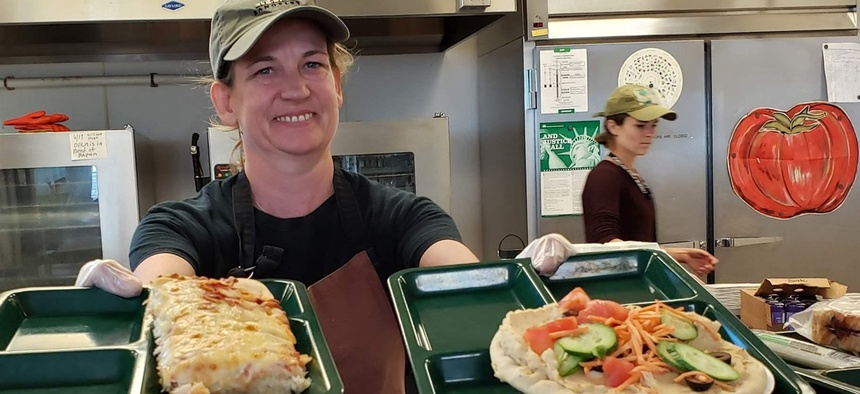 Portland, Maine, school cafeteria worker Alison Mason shows off lunch options at East End Community School, including traditional pizza, left, and vegan pizza with hummus and vegetables.