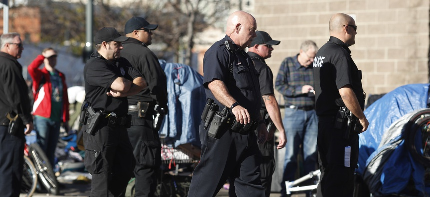 Denver Police Department officers keep watch during a sweep of homeless people who were living on the walks surrounding a shelter near the baseball stadium Tuesday, Nov. 15, 2016, in downtown Denver.