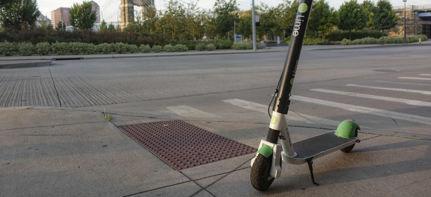 A Lime electric rental scooter parked near a crosswalk awaits a user.