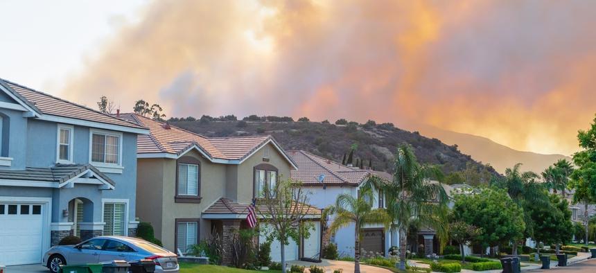 A wildfire burns near homes in Corona, California.