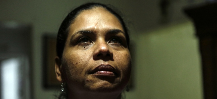 Wanda Gomez, a survivor of domestic violence, poses in her home, in Miami, Fla. According to Gomez, she lost her job and home after being stabbed nearly to death by an ex-boyfriend.