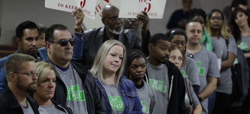 """In this Sunday, Nov. 3, 2019, photo, people wearing """"Save The Paseo"""" shirts stand among attendees at a rally to keep a street named in honor of Dr. Martin Luther King Jr. at the Paseo Baptist Church in Kansas City, Mo."""