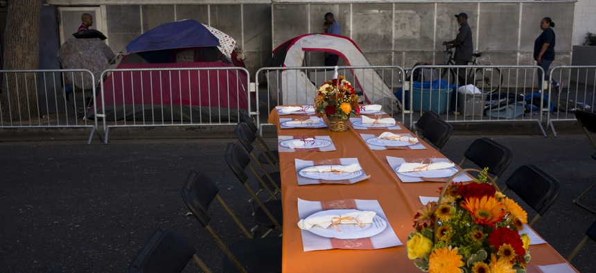 Homeless tents are pitched on a sidewalk in the Skid Row area of downtown Los Angeles Wednesday, Nov. 22, 2017, as tables are set up on the street to serve dinner to homeless people at the Los Angeles Mission's Annual Thanksgiving Dinner Celebration.