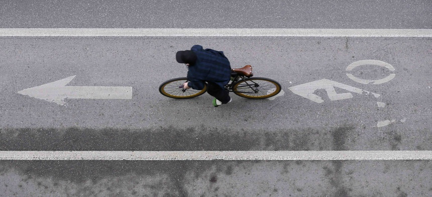 In this Monday, March 14, 2016, photo, a cyclist rides in a bike lane on a downtown street, in Des Moines, Iowa.