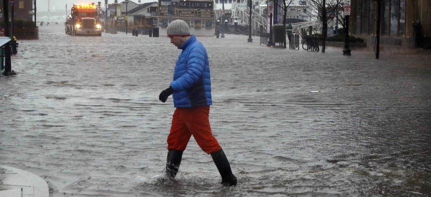 A man walks through water covering State Street in Boston, flooded by water from Boston Harbor at high tide during a major nor'easter that pounded the East Coast, Friday, March 2, 2018.