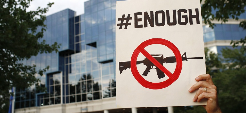 Protester Matt McCabe holds a sign outside the National Rifle Association's headquarters building during a vigil for recent victims of gun violence, Monday, Aug. 5, 2019, in Fairfax, Va.
