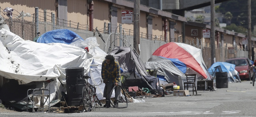 A man holds a bicycle tire outside of a tent along a street in San Francisco.
