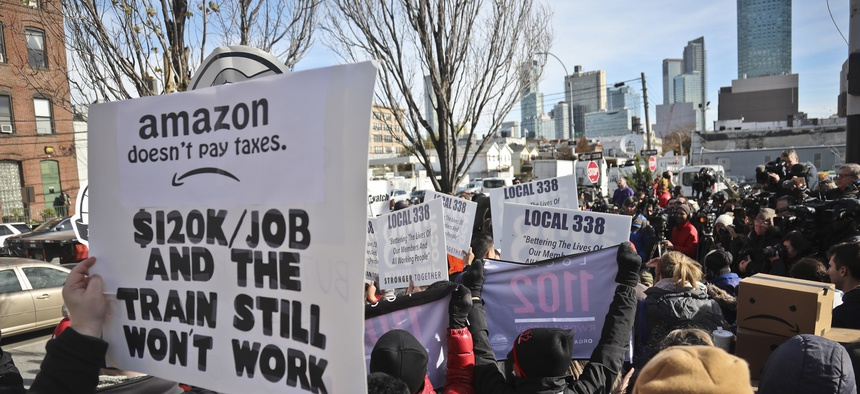 In this Nov. 14, 2018, file photo protesters carry anti-Amazon posters during a coalition rally and press conference opposing Amazon headquarters getting subsidies to locate in the New York neighborhood of Long Island City.