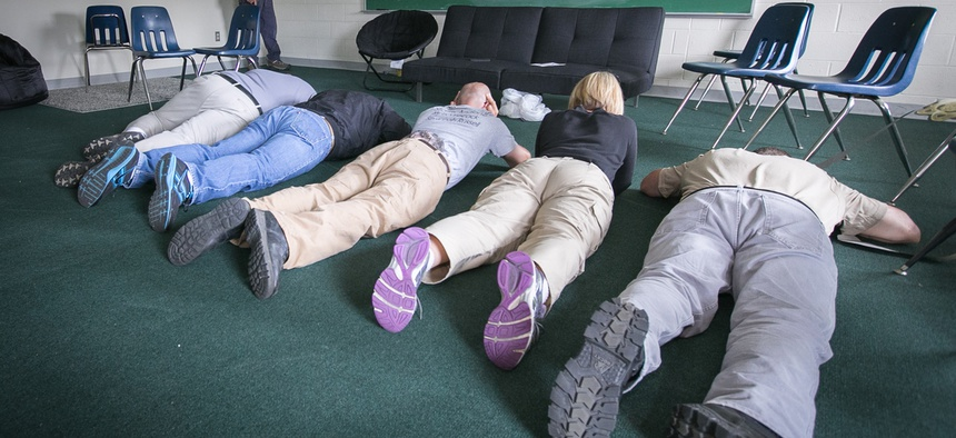 School employees play dead on the floor during an active shooter mock scenario in Rittman, Ohio, in June 2014.