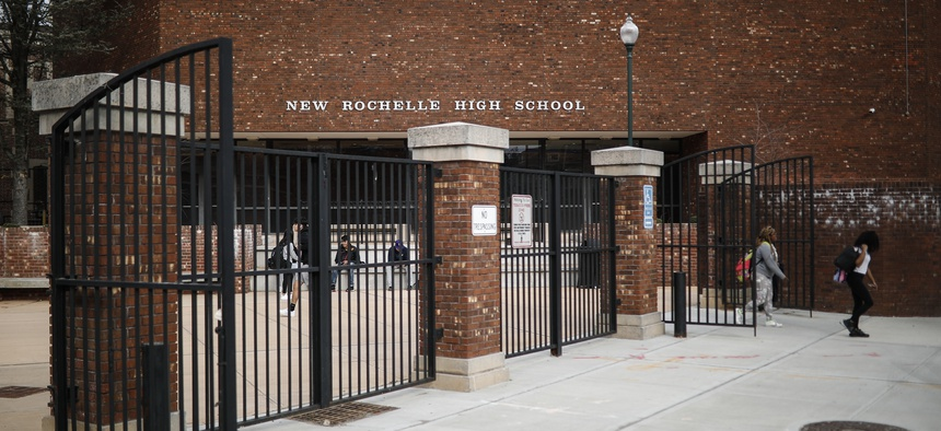 Students leave New Rochelle High School after classes are dismissed, Tuesday, March 10, 2020, in New York. State officials are shuttering schools and houses of worship for two weeks in part of the New York City suburb New Rochelle.