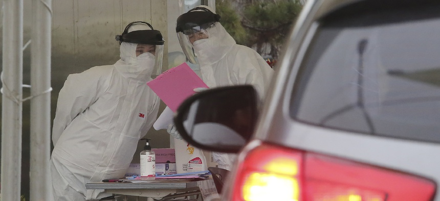 """Medical staffers wearing protective suits work to take samples from drivers with suspected symptoms of the coronavirus at a """"drive-through"""" virus test facility in Goyang, South Korea on March 1, 2020."""