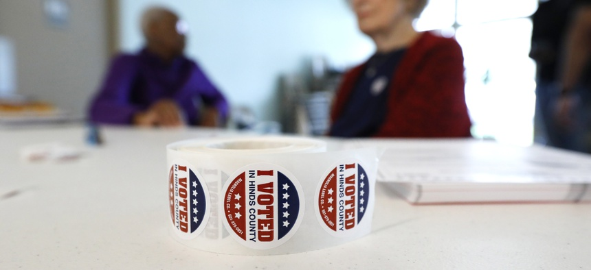 """A roll of """"I Voted"""" stickers rests next to ballots as poll workers wait for voters at a Jackson, Miss., precinct, Tuesday, March 10, 2020."""