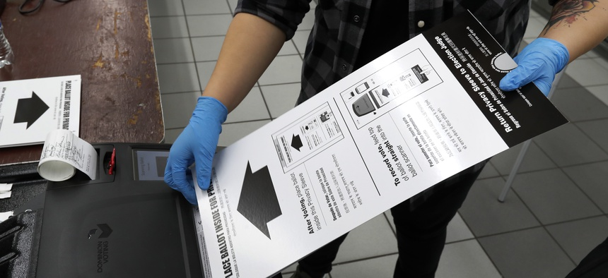 A poll worker at the Su Nueva Lavanderia polling place uses rubber gloves as she enters a ballot in the ballot box Tuesday, March 17, 2020, in Chicago.