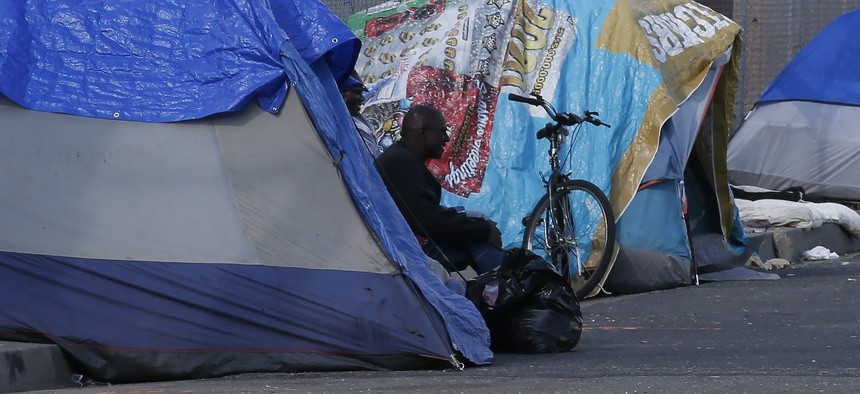 A homeless man sits in a tent in Sacramento, Calif., Friday, March 20, 2020. Gov. Gavin Newsom has authorized $150 million in emergency funding to protect homeless people in the state from the spread of COVID-19.
