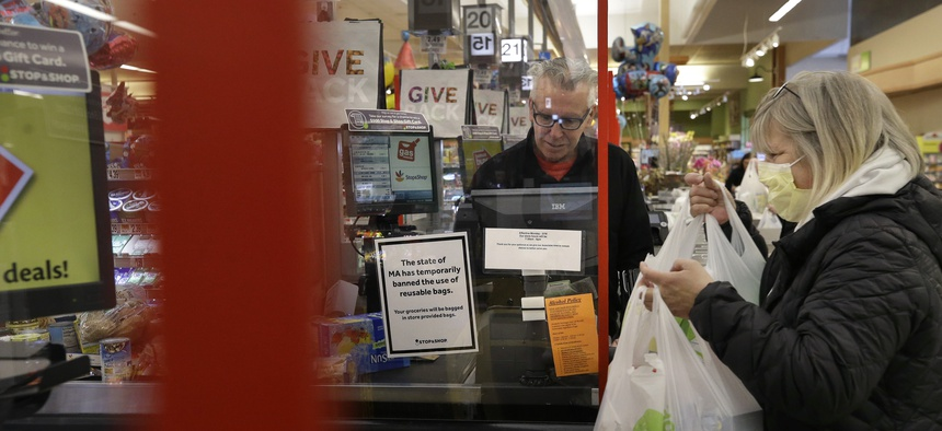 A cashier at a grocery store in Quincy, Mass., center, works behind a plastic shield as a shopper, right, places groceries in a cart.