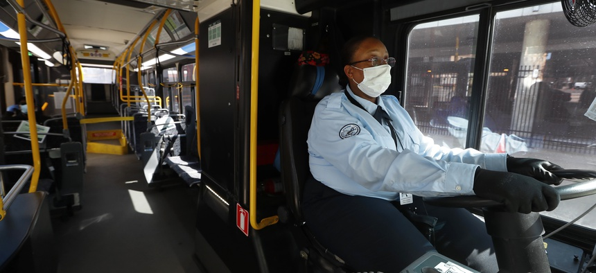 Detroit bus driver JaVita Brown wears gloves and a protective mask during the COVID-19 outbreak. City buses will have free surgical masks available to riders starting Wednesday, a new precaution the city is taking.